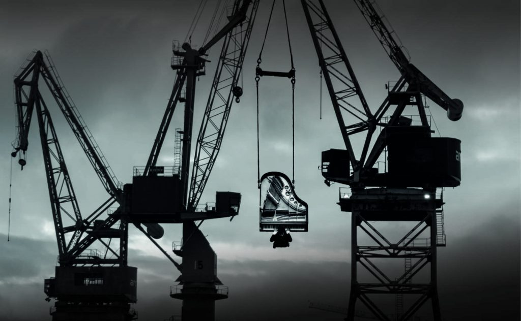 Promotional image of a piano suspended from two cranes