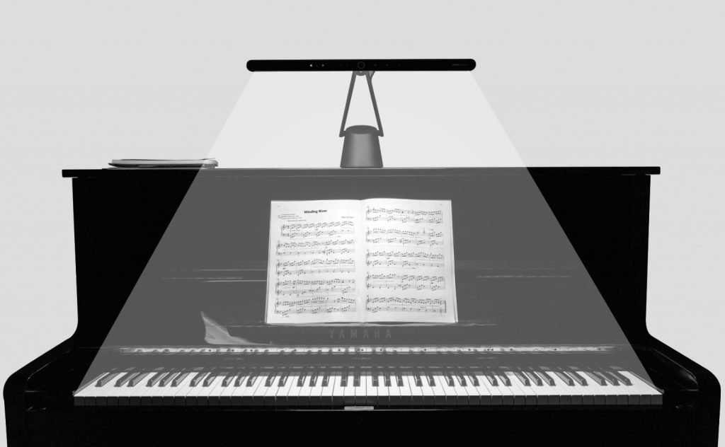 A PianoLight sat on top of an upright piano showing the beam from the lamp
