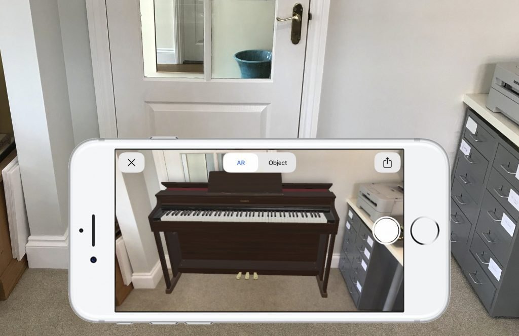 Image showing iPhone with a virtual Casio digital piano positioned in the empty space of the room