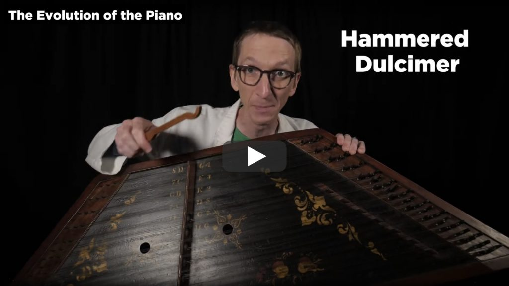 screenshot from Part 1 of The Evolution of the Piano video featuring Evan the Educator holding a hammered dulcimer