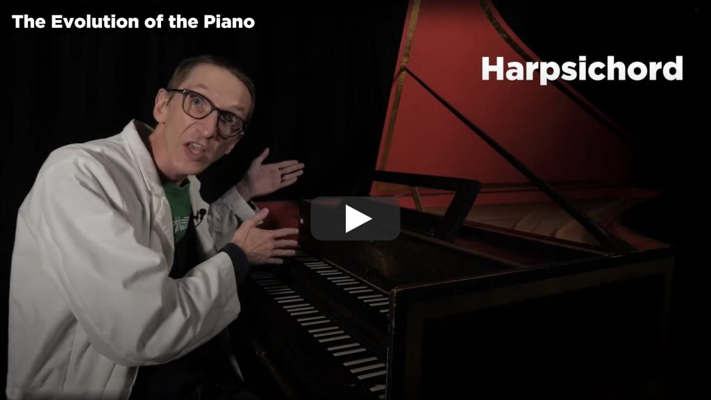 A screenshot from Part 3 of The Evolution of the Piano video.  This shows Evan the Educator gesticulating towards a harpsichord