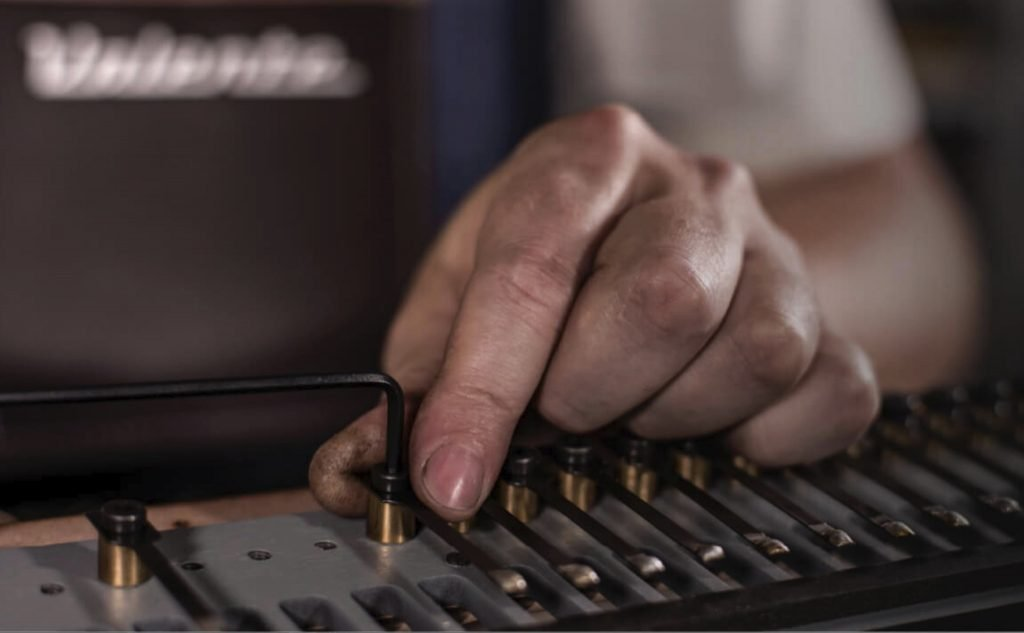 image showing technician bolting the reeds to the pianos harp