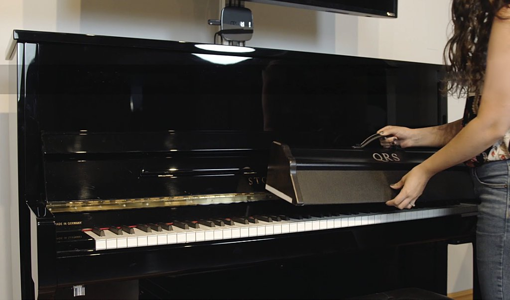 image showing the QRS UV Keyboard Sanitizer being placed on a Story & Clark upright piano