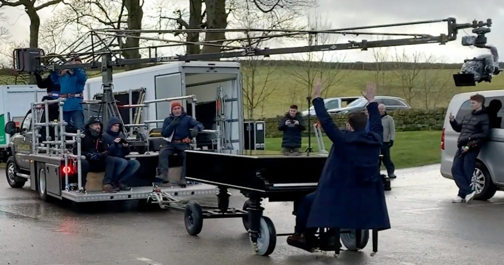 picture of the piano on a trailer being towed behind the camera truck. Cameras are mounted around the piano.