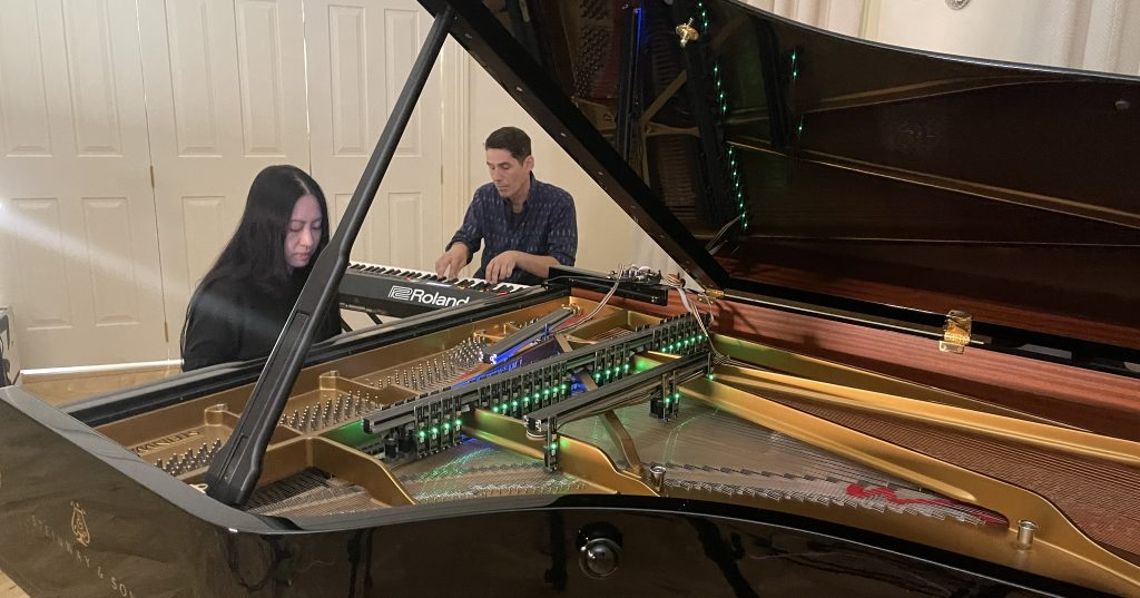 photo of Monica Lim seated at a Steinway fitted with the Electromagnetic Piano system with David Shea sat alongside at a Roland keyboard