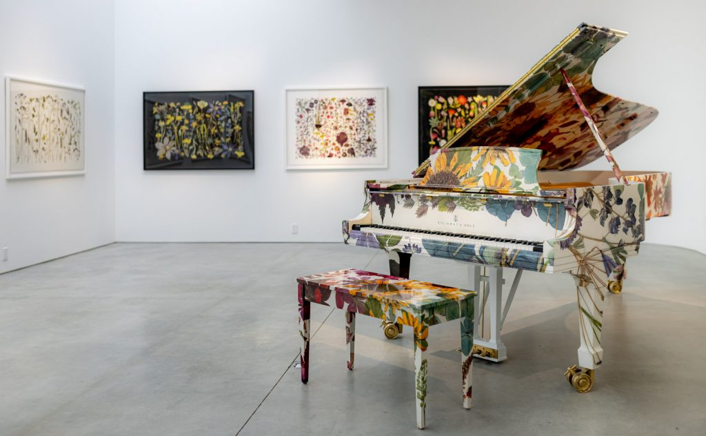 Paoluccio's piano on display at the  High Line Nine Gallery in front of a collection of other floral-based artworks.