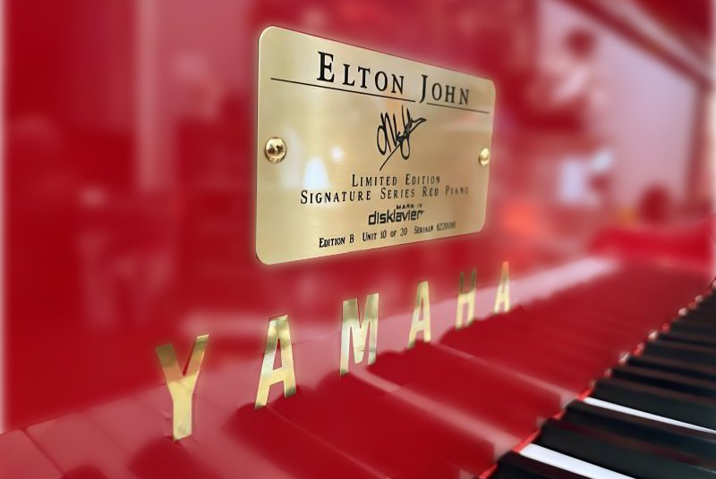 close up of the brass plaque of the Yamaha Elton John Limited Edition Signature Red piano