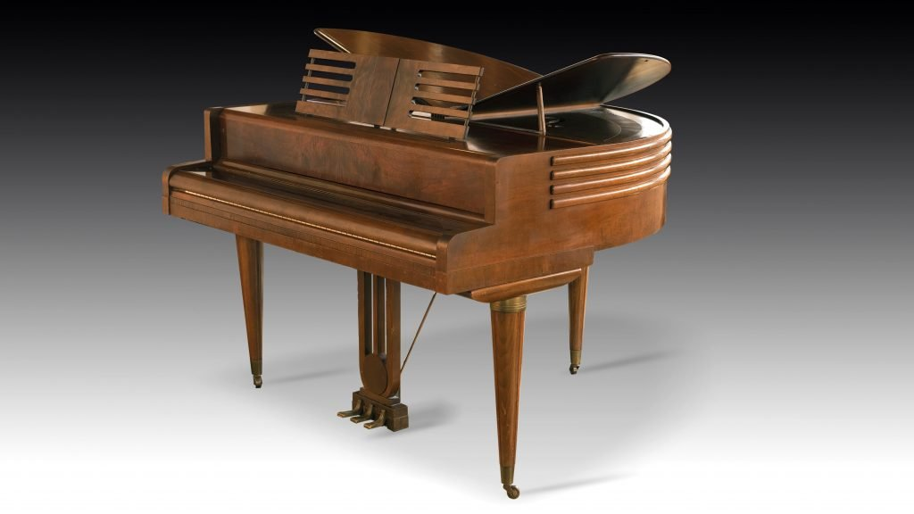studio photograph of Wurlitzer piano with fallboard closed and split lid (wings) open