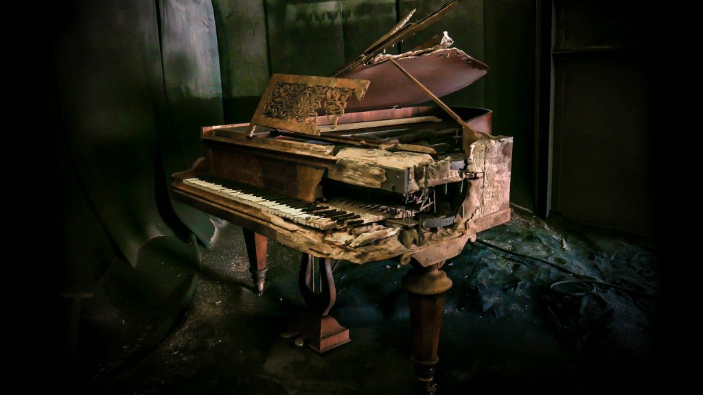 """photo of sandblasted grand piano with half one side """"blown"""" away."""